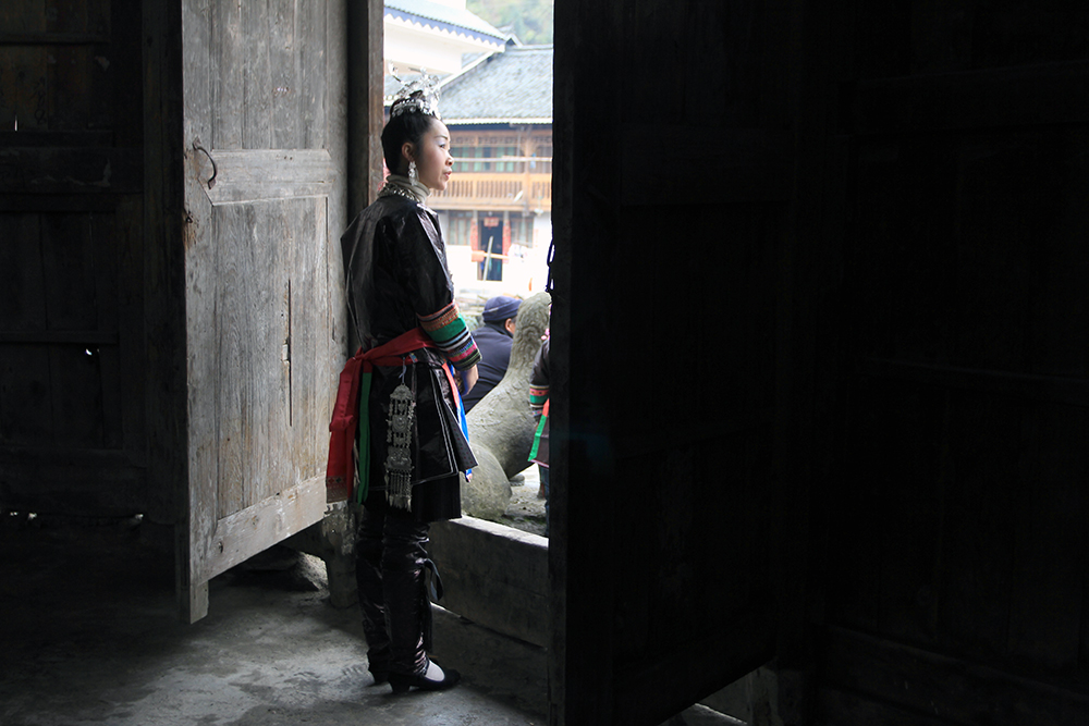 A girl in village drum tower is waiting for her friends from village nearby to the festival